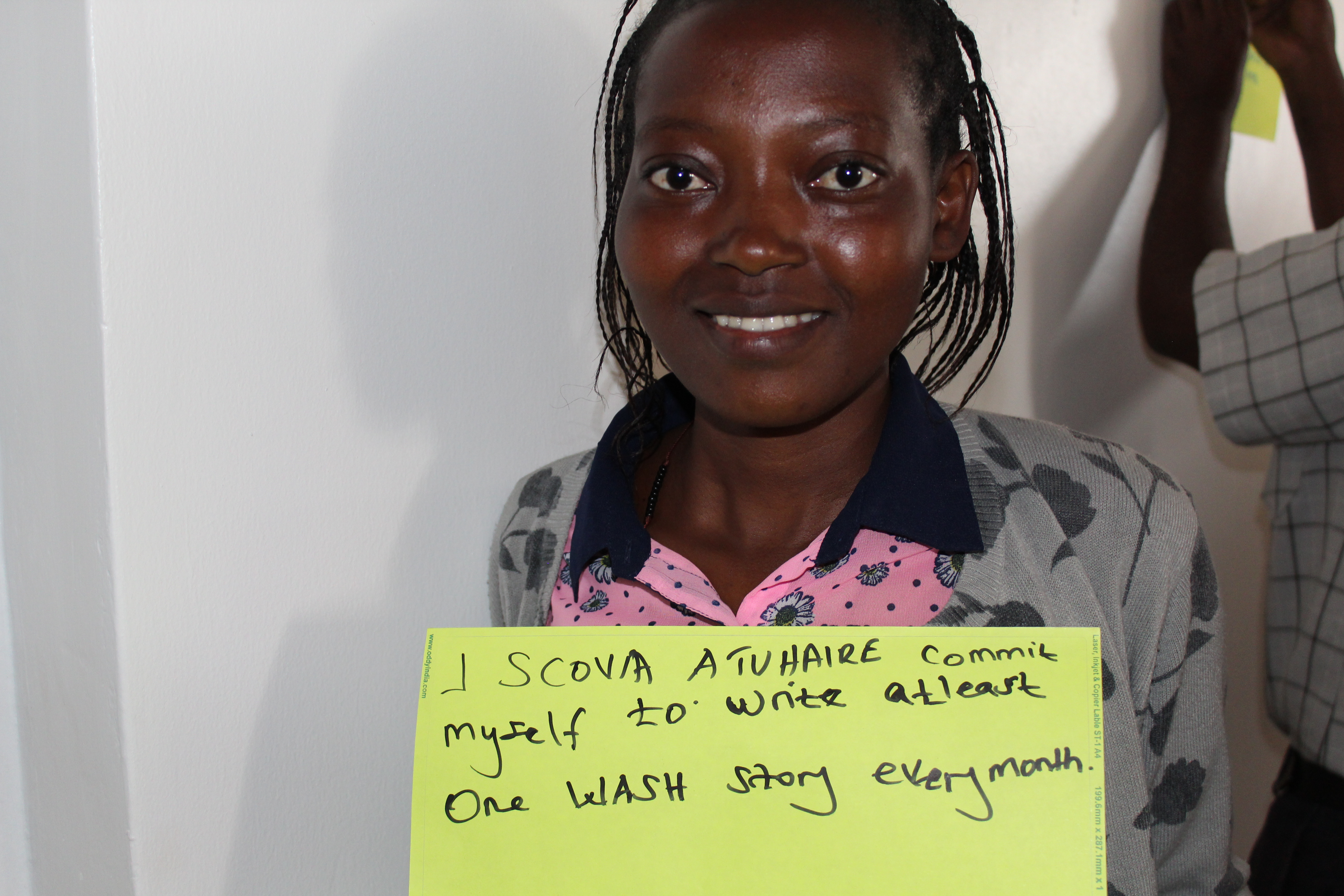 A journalists holds up a placard stating her commitment to WASH coverage