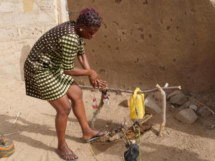 Jennifer Nyaaba, WSMT advocacy team secretary, uses a tippy tap outside her house to wash her hands