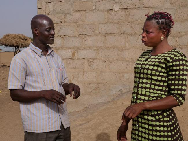 Bongo District Environmental Health Officer Mumuni Abdulai discusses sanitation with Jennifer Nyaaba, a member of the Asaloko Water and Sanitation Management Team