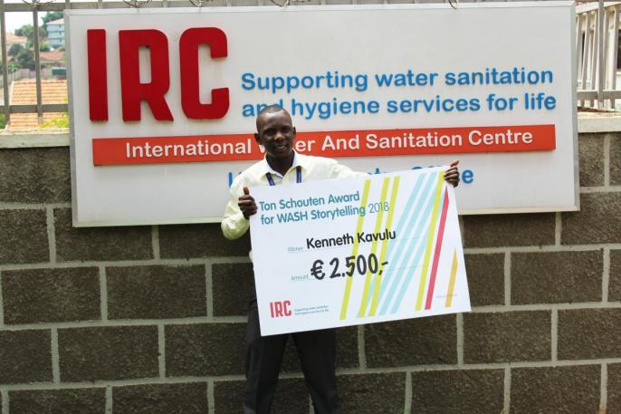 Kenneth Kavulu in front of IRC Uganda's office with a cheque announcing his 2500 euro cash award