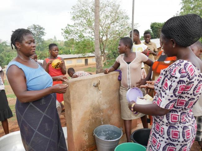 Paying the caretaker at the water point in Ghana