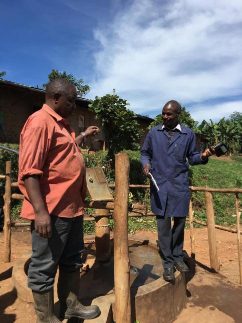 Stephen Balyabuga of KAHASA talks with the Burungu Water User Committee Chairperson (Photo by Caleb Cord)