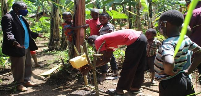 A family demonstrates to the monitoring team how they practise handwashing at home using a tippy tap
