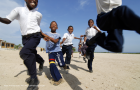 Colombia, Tierrabomba, group of excited schoolchildren running together against sky