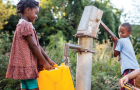 Girl and boy fetching water at handpump