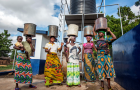 African women with water buckets on their heads. Photo: Simavi
