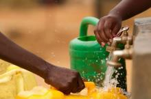 Close up of a hand carrying container being filled with water at tap stand