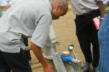 A hand pump mechanic checks on the functionality of a newly rehabilitated borehole