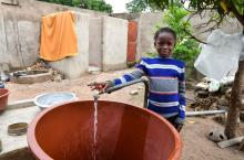 Girl near tap in Burkina Faso