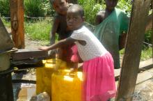 Children fetch water from a newly-rehabilitated borehole, in Kasenyi village, Kabarole District