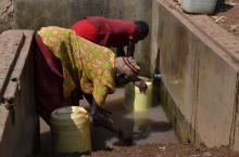 Users collect water from a protected spring in Namayingo District, Uganda