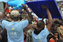 Two men displaying plastic sanitation products to a crowd