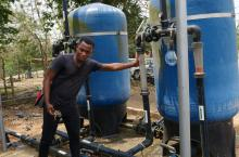 Eric Christford Mensah, CWSA technical engineer, demonstrates the alkaline treatment system that purifies water at Ekutuase