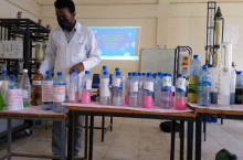 A trainer demonstrating the process of producing liquid soap in laboratory setting
