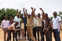 Happy men at a working water pump in Ghana