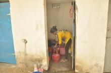 Woman cleaning toilet - Odisha, India