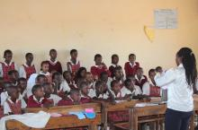 Young girls listening to teacher talking about menstrual hygiene in Kenya