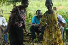 USF technical staff dances with a community member in Agelilyec village