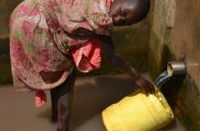 A girl fetches water from a protected spring well in Namayingo district