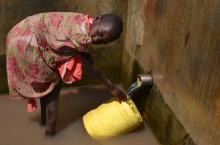 Fetching water from a protected spring well in Lira district