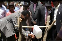 Minister of Water and Environment Sam Cheptoris uses a tippy-tap at World Wate Day event, Uganda
