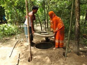 Bangladeshi couple constructing latrine