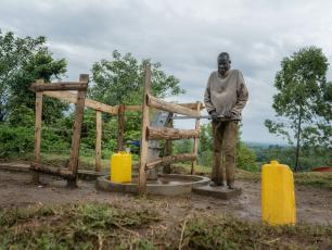 Man pumping water in Uganda