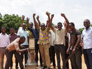 Happy men at a working water pump in Ghana