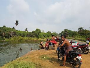 People bathing and washing clothes in a river. Chatrapur Block, Ganjam District, Odisha state, India.