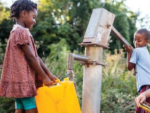 Girl and boy fetching water at handpump