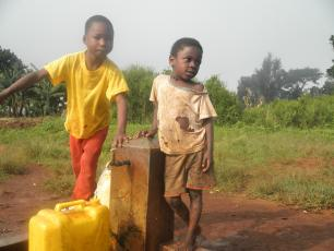 Children fetch water from a tap in Kabarole district