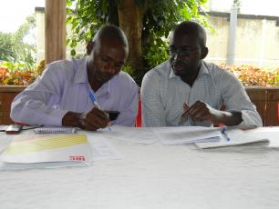 Hand Pump Mechanic Stephen Baryebuga (left) has a discussion with the District Water officer, Pius Mugabi