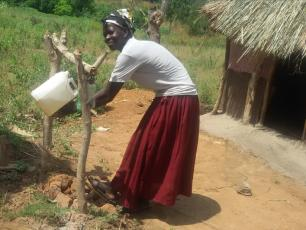 A lady, Esther, demonstrates the use of a tippy tap in Moyo District