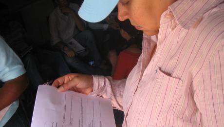 Woman checking paper. El Manantial. Tegucigalpa. Honduras