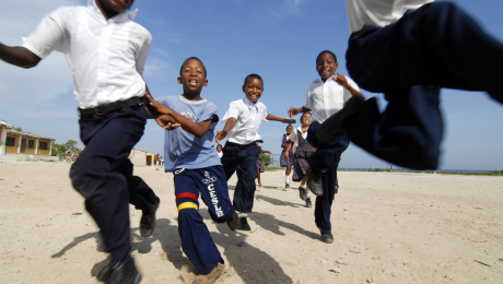 Anthony Asael, Colombia, Tierrabomba, group of excited schoolchildren running together against sky
