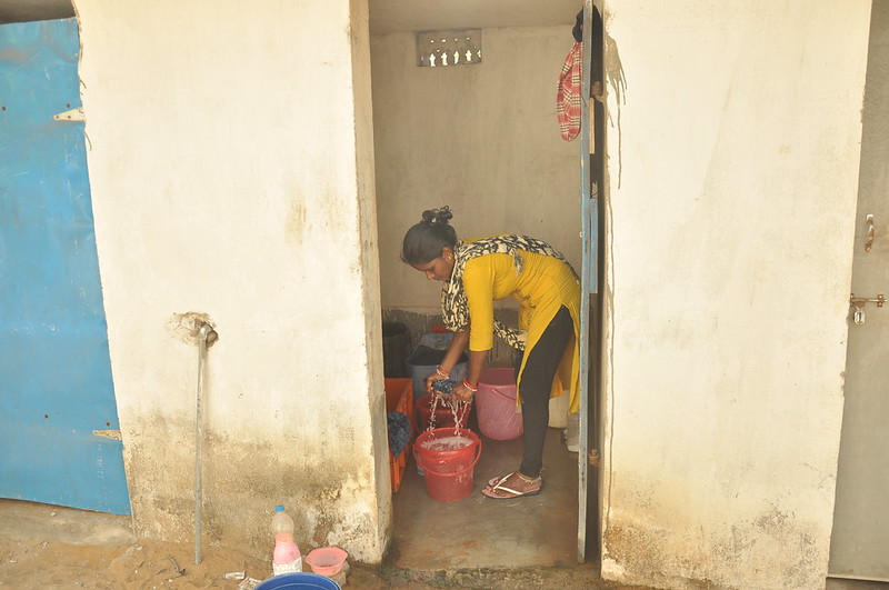 Woman cleaning toilet, Odisha, India