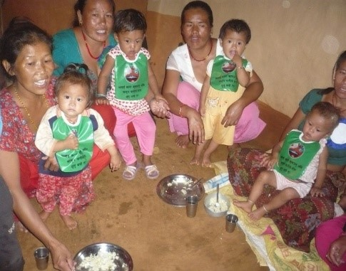 Mother with babies wearing bibs with hygiene messages