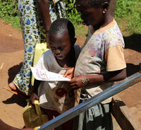 Children study a leaflet telling them how to report a fault at their water point. Karambi sub-county, Kabarole, Uganda.